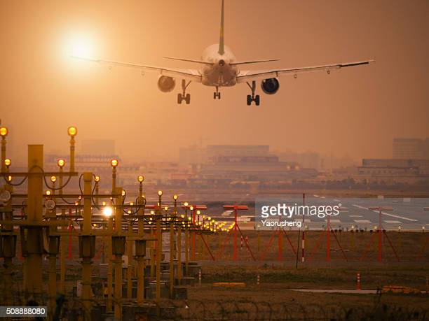Airplane landing at Shanghai Hongqiao Airport. Runway lights in the foreground.