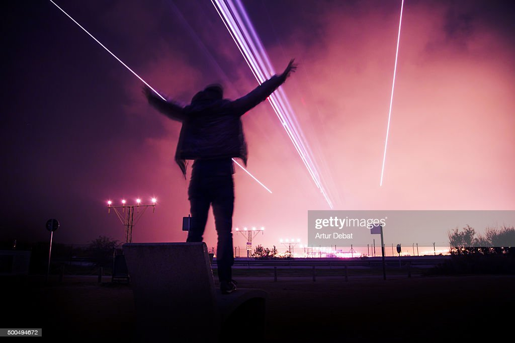Airplane landing in the Barcelona El Prat airport at night with excited man with arms raised. : Stock Photo