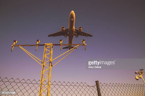 Airplane landing in the Barcelona El Prat airport from below with the airplane belly and the track lights.