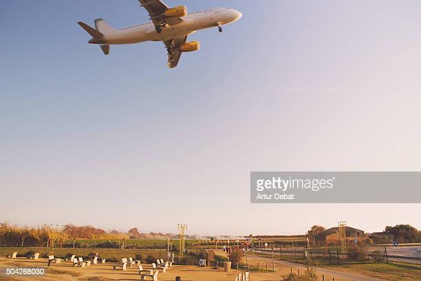 Airplane landing in the Barcelona El Prat airport over the viewpoint near the track.