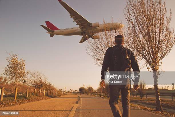 Airplane landing in the Barcelona El Prat airport with people walking in the Llobregat delta nature reserve.