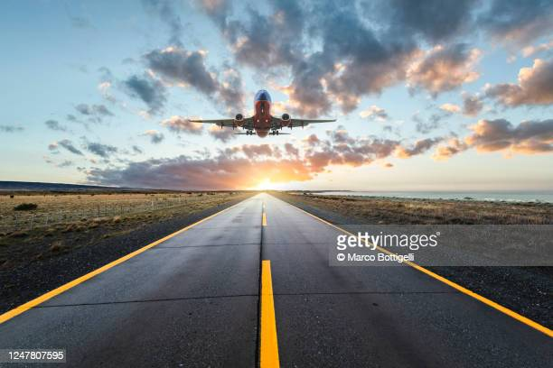 airplane landing on a road at sunset - 飛び立つ ストックフォトと画像