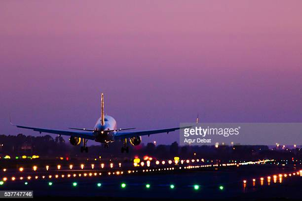 Airplane landing on the Barcelona airport at night with nice detail view of the illuminated track, aircraft and purple sky.