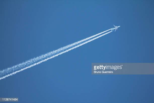 airplane leaving vapor trail behind against blue sky - flugzeug stock-fotos und bilder