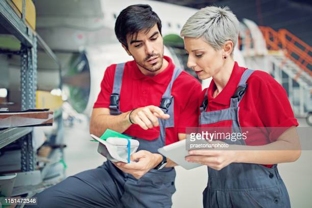 airplane mechanics are choosing parts for planned aircraft maintenance in the hangar - spare part stock pictures, royalty-free photos & images