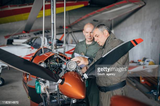 airplane mechanics repairing propeller airplane together - air vehicle stock pictures, royalty-free photos & images
