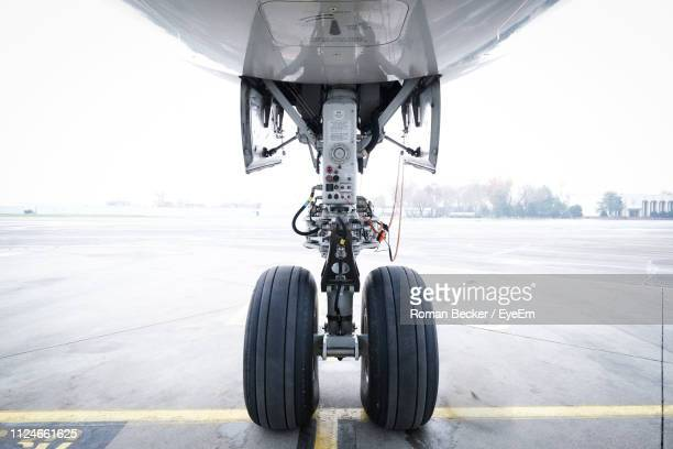airplane on airport runway against sky - wheel stock pictures, royalty-free photos & images