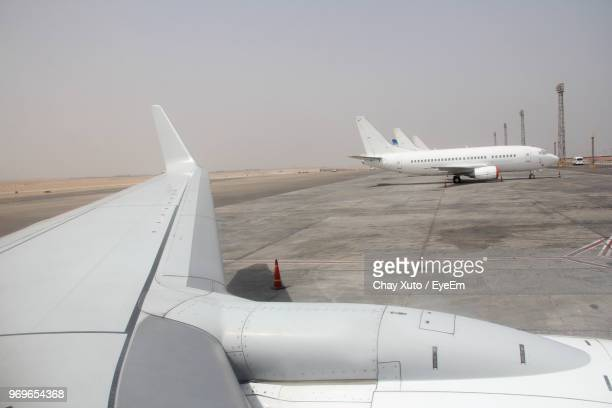 airplane on airport runway against sky - delhi airport stock photos and pictures