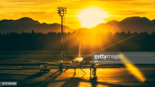 Airplane on airport runway at sunset