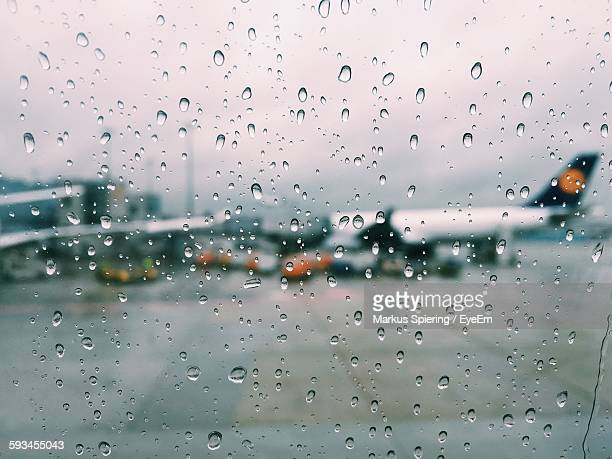 Airplane On Airport Runway Seen Through Wet Glass Window During Monsoon