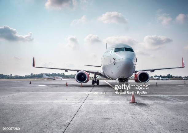 airplane on runway against sky - aeroplane stock pictures, royalty-free photos & images