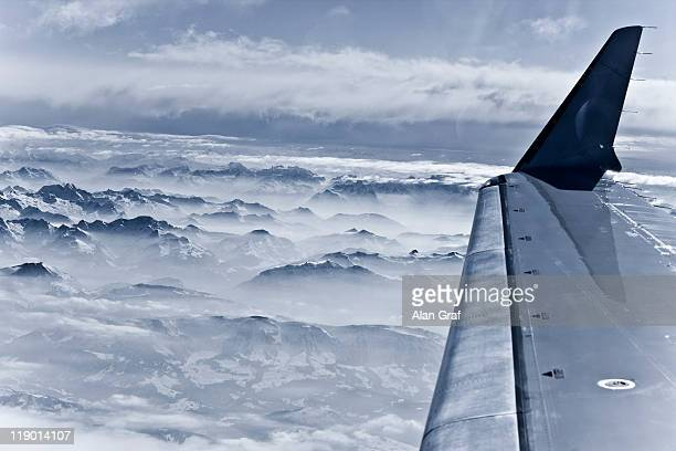 airplane over snow covered mountains - airplane part stock photos and pictures