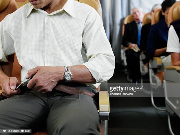 Airplane passenger fastening seatbelt