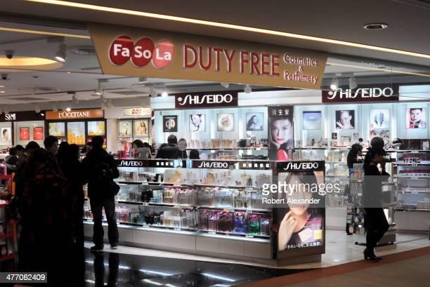 Airplane passengers between flights browse at a FaSoLa duty free cosmetics and perfume shop at Narita International Airport near Tokyo.
