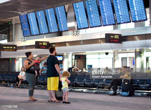 Airplane passengers consult an airport departure board at Denver International Airport in Denver Colorado