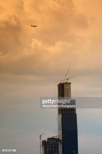 Airplane passing by a skyscrapper