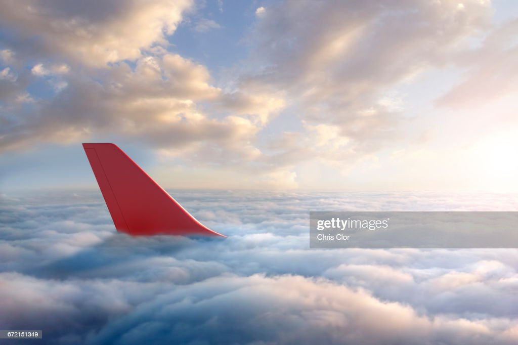 Airplane rudder above clouds : Stock Photo