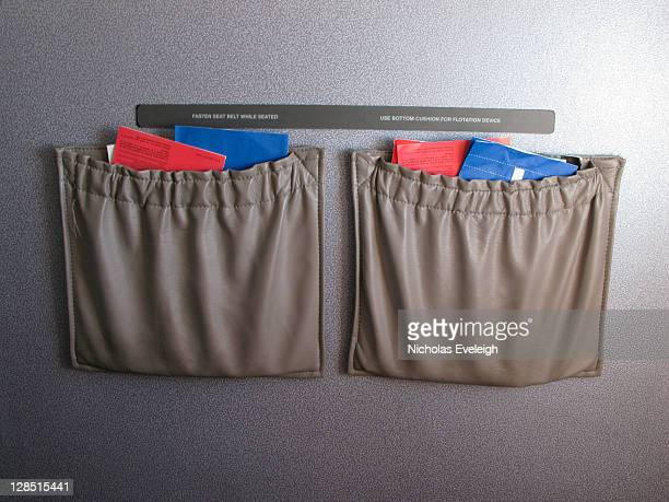 airplane seat pockets with instructions and sickness bag - vehicle seat stock pictures, royalty-free photos & images