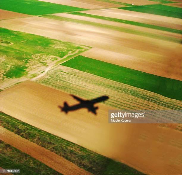 Airplane shadow on farm fields in Austria