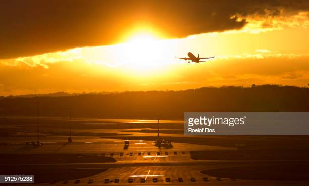 Airplane taking of at Hamburg airport in Germany during sunset with dramatic sky