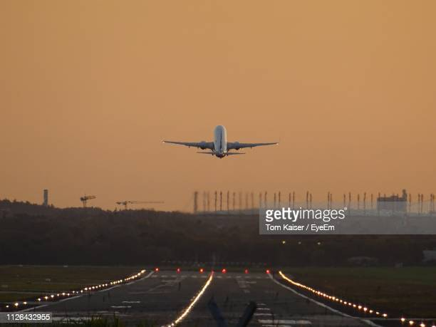 airplane taking off against sky during sunset - 飛び立つ ストックフォトと画像