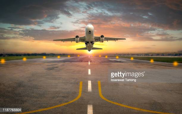 airplane taking off from the airport runway in beautiful sunset light - aeroplane stock pictures, royalty-free photos & images