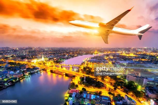 Airplane transportation flying above the Bangkok night city, Thailand.