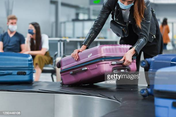 airplane traveler wearing n95 face mask receiving luggage from conveyor belt - vacations stock pictures, royalty-free photos & images