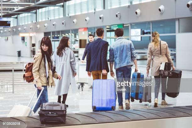 viajeros de avión llevando equipaje de cinta transportadora - izusek fotografías e imágenes de stock