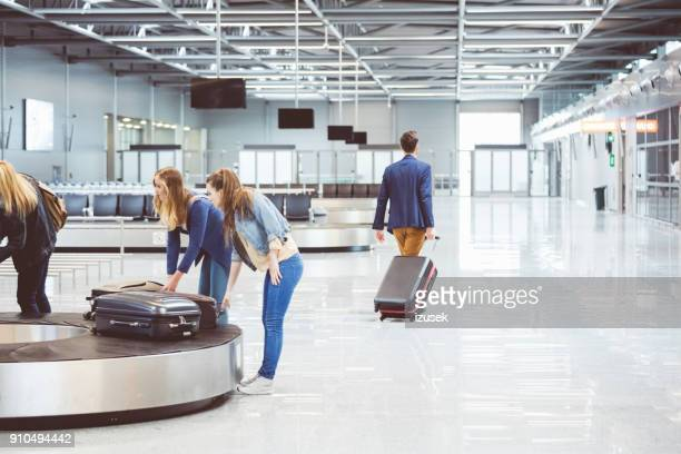airplane travelers waiting for luggage near conveyor belt - airport terminal stock photos and pictures
