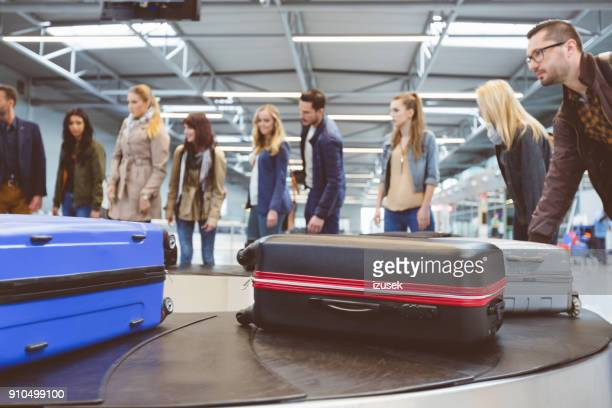 airplane travelers waiting for luggage near conveyor belt - baggage claim stock pictures, royalty-free photos & images