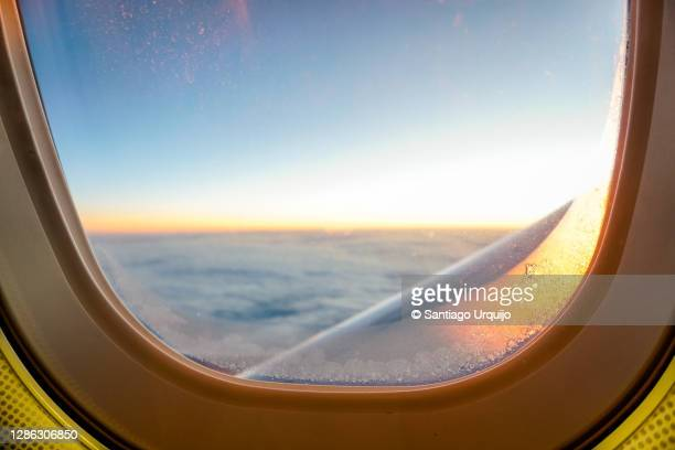 airplane window covered partially in ice while flying - capital region stock pictures, royalty-free photos & images