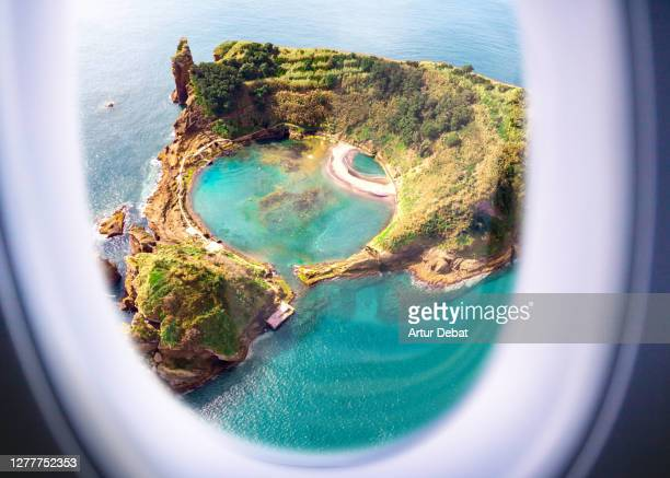 airplane window view from passenger point of view of a small island with lake inside in the azores. - azores fotografías e imágenes de stock