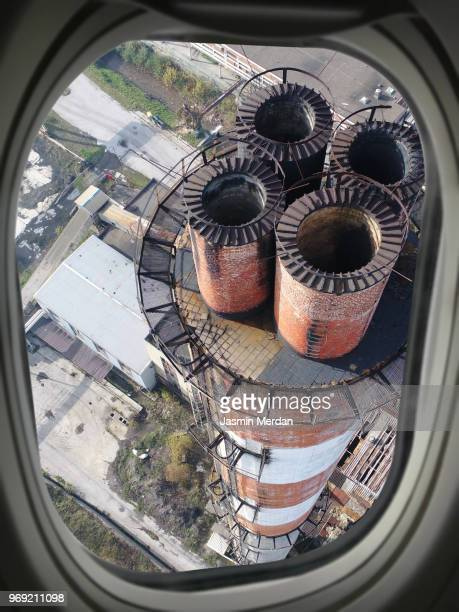 Airplane window view of industry chimney