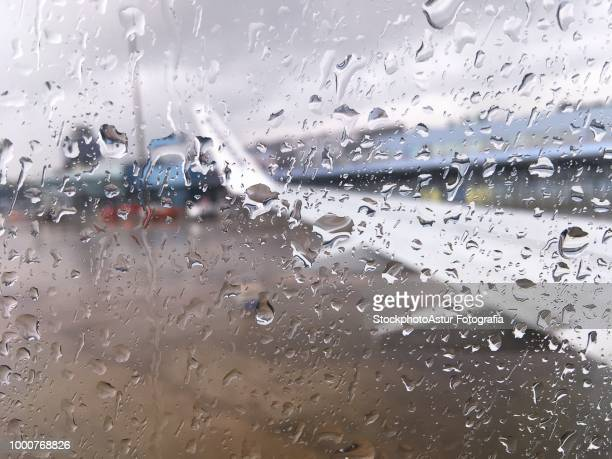 Airplane window with drops of water at the airport.