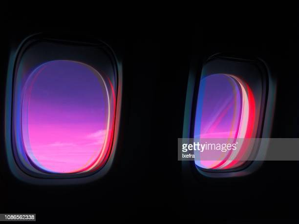 Airplane windows in dramatic, colorful light