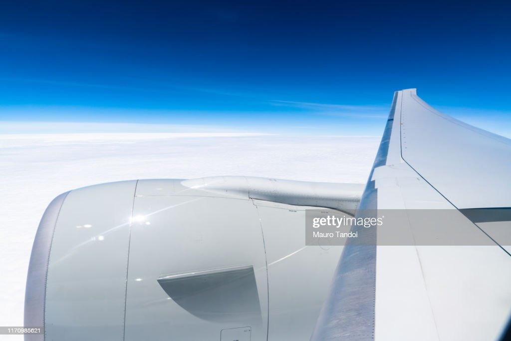 Airplane wing against clear blue sky : Stock Photo
