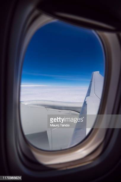 airplane wing against clear blue sky - mauro tandoi stock pictures, royalty-free photos & images