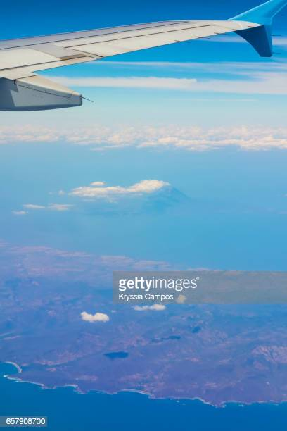 Airplane wing flying above coastline