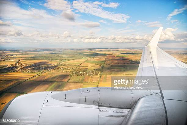 Airplane wing flying above the fields in Hungary