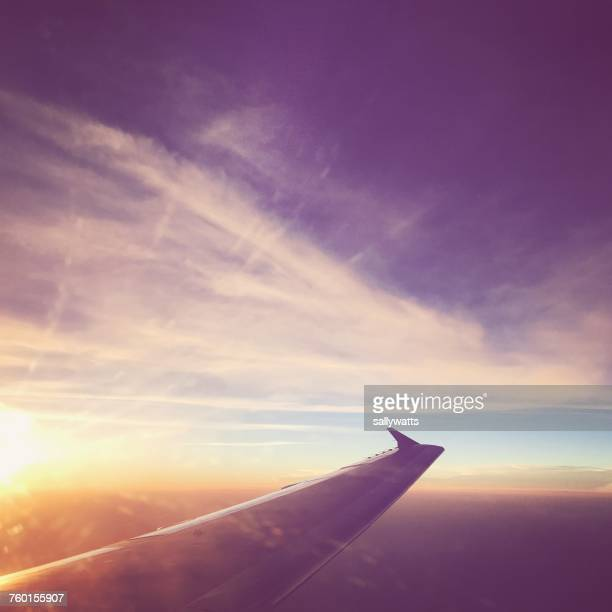 Airplane wing in sky at sunset
