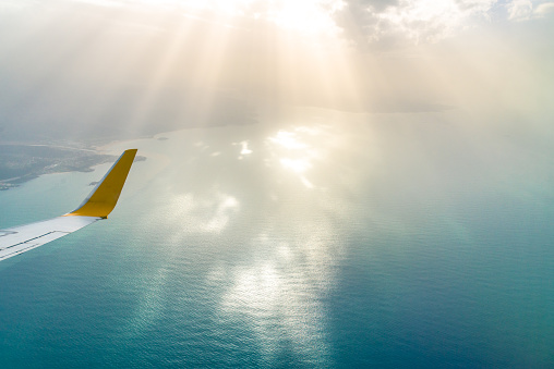 Airplane wing with sun beam and the sea in a background - gettyimageskorea
