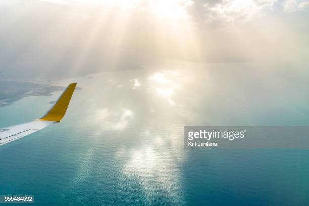 Airplane wing with sun beam and the sea in a background