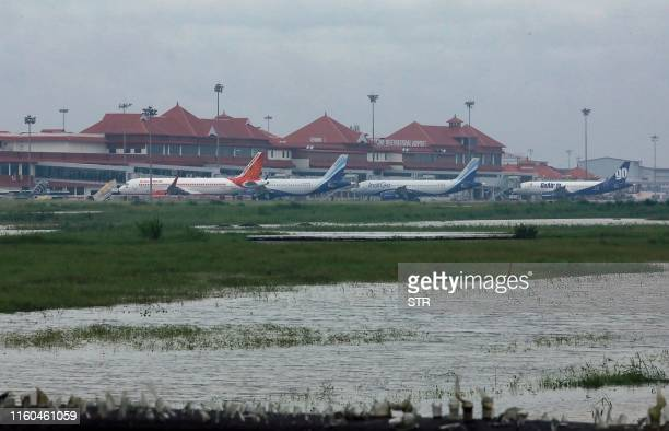 Airplanes are pictured as they are parked next to flood waters on the tarmac of the international airport in Kochi in southern Kerala state on August...