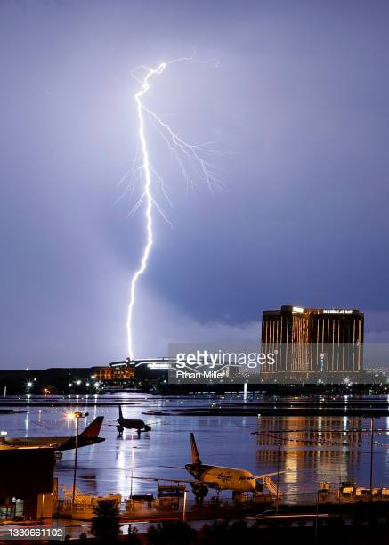 Airplanes are shown parked at McCarran International Airport as lightning strikes west of Allegiant Stadium and Mandalay Bay Resort and Casino during...