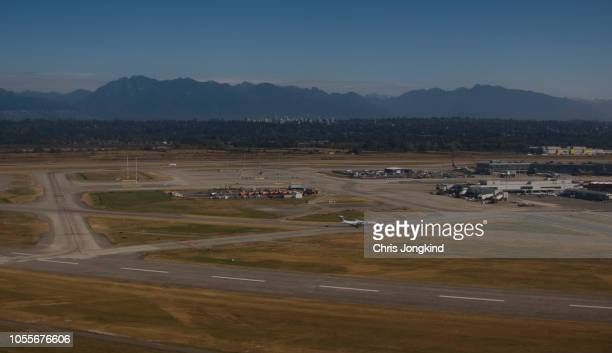 airplanes at runways at an airport in the mountains - vancouver international airport stock pictures, royalty-free photos & images
