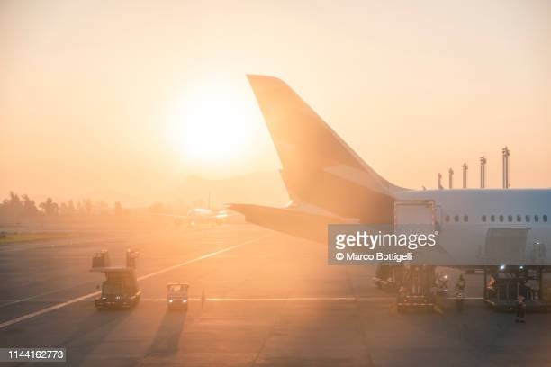 airplanes at the airport at sunrise - voar imagens e fotografias de stock