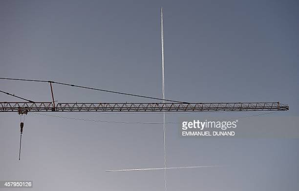 Airplanes cross paths in the sky above a crane in Brussels on October 27 2014 AFP PHOTO/Emmanuel Dunand
