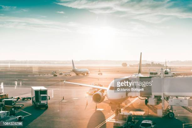 airplanes in an airport at sunrise - flughafenterminal stock-fotos und bilder