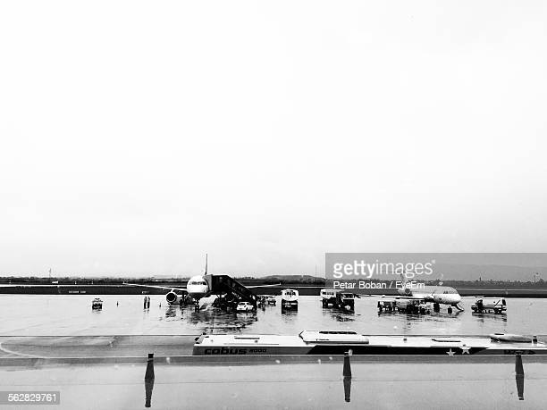 airplanes on wet runway at zagreb international airport against clear sky - boban stock pictures, royalty-free photos & images